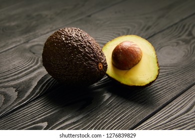 Image of avocado on black wooden background