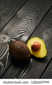 Image of avocado on black wooden background with copyspace