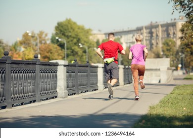 Image from back of athletic pair running along promenade
