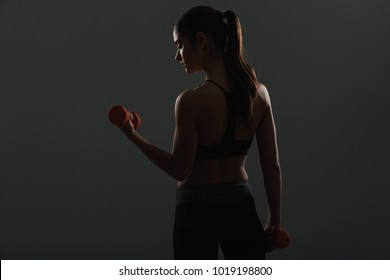 Image from back of slim sporty woman doing exercises with small red dumbbells isolated over gray background