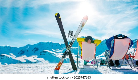 Image from back of vacationers in armchair, skis, sticks in snowy resort