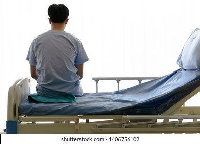 Image of the back of a young man wearing the patient suit sitting alone on the hospital bed looking out of the window thoughtfully worrying.