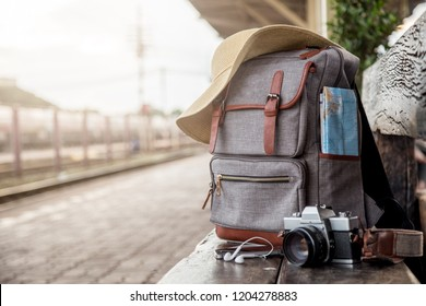 Image backpack, Mobile phone, earphone, map, hat and camera film on floor at the train station. Travel concept. vintage style.