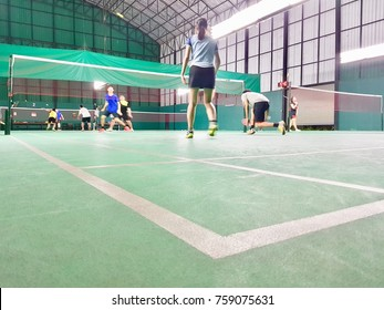 An image of a badminton tournament seen from the corner of the court.