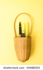 image of a basket on an orange background with pens in it