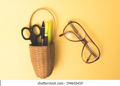 image of a basket on an orange background with pens ,scissors in it and spects beside it