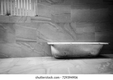 The image of bathtub and concrete wall with empty space in black and white style.