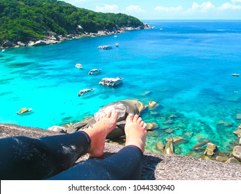 The image of the bay of Similan Islands. View from female legs