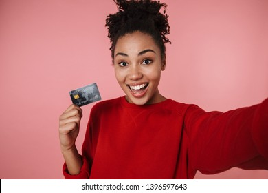 Image of a beautiful amazing happy excited young african woman posing isolated over pink wall background take selfie by camera with credit card.