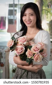 Image of a beautiful Asian woman with smiling face. And a bouquet of pink roses in her hand.