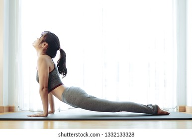 Image of beautiful Asian young woman practicing yoga indoor. Calmness and relax, female happiness.Horizontal, blurred white background.