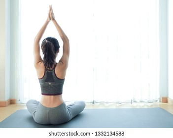 Image of beautiful Asian young woman practicing yoga indoor. Calmness and relax, female happiness. White background.