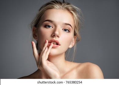 Image with beautiful blonde girl touching her lips on grey background. Beauty & Skin care concept - Shutterstock ID 765380254