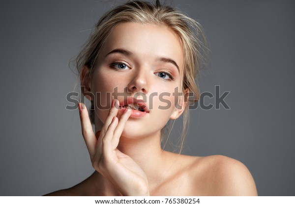 Image with beautiful blonde girl touching her lips on grey background. Beauty & Skin care concept
