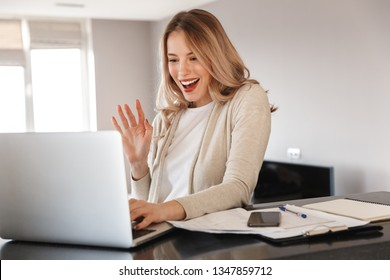 Image of a beautiful blonde woman posing sitting indoors at home using laptop computer talking waving.