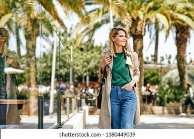 Image of beautiful blonde woman smiling and looking away, during her vacation. Attractive female walking on the city street, relaxing on sunny day, against palms background with copy space. Lifestyle