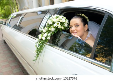 Image of beautiful bride showing her rose bouquet out of wedding limousine and looking at camera