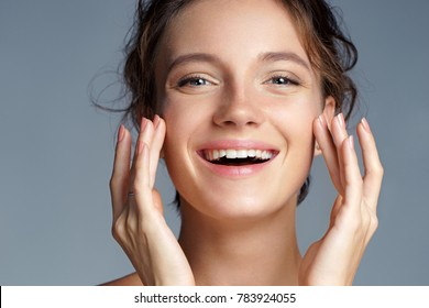 Image with beautiful brunette girl touching her face on grey background. Close up. Beauty & Skin care concept