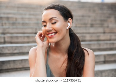 Image of beautiful brunette woman 20s with dark hair in ponytail sitting on street stairs on summer day while listening to music via bluetooth earbud
