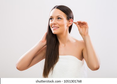 Image of beautiful brunette woman cleaning ear.