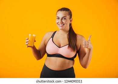 Image of beautiful chubby woman in tracksuit smiling and holding glass with orange juice isolated over yellow background