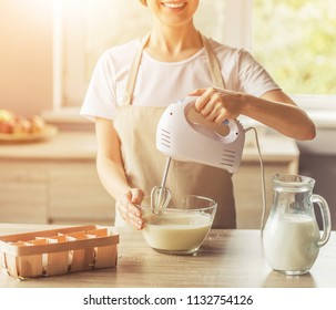 Image of Beautiful Cute Woman in Apron Smiling. Mom Mixing Liquid Dough for Baking Using Electric Mixer in Modern Kitchen at Sweet Home. Mother Cooking Happiness Activitiy Home Concept.