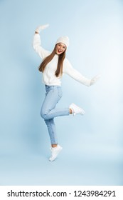 Image of a beautiful cute young woman wearing winter hat posing isolated over blue wall background.
