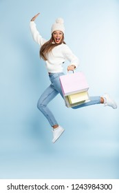 Image of a beautiful cute young woman wearing winter hat jumping isolated over blue wall background holding holding shopping bags.
