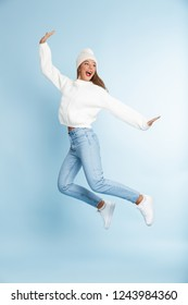 Image of a beautiful cute young woman wearing winter hat jumping isolated over blue wall background.