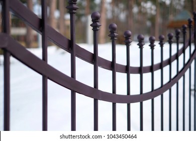 Image of a Beautiful decorative cast metal wrought fence with artistic forging. Iron guardrail close up.