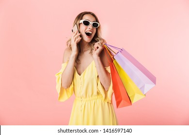 Image of a beautiful excited happy young blonde woman posing isolated over pink wall background holding shopping bags talking by mobile phone.