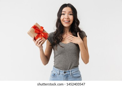 Image of a beautiful excited young woman posing isolated over white wall background holding present box.