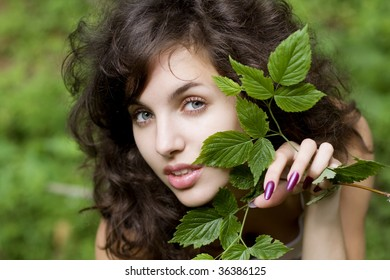 Image of a beautiful girl with a green branch in his hands