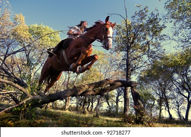 Image of Beautiful girl with purebred horse, jumping a hurdle in forest