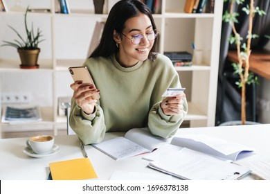 Imagen de una bella joven y optimista joven estudiante en casa que estudia usando el teléfono móvil con tarjeta de crédito.