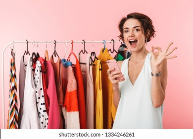 Image of a beautiful happy woman stylist posing isolated over pink wall background near a lot of clothes using mobile phone.