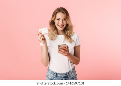 Image of a beautiful happy young blonde woman posing isolated over pink wall background holding credit card using mobile phone.
