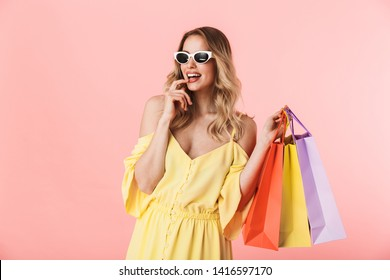 9366e08b8 Image of a beautiful happy young blonde woman posing isolated over pink  wall background holding shopping