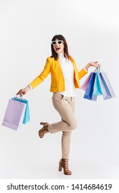 Image of a beautiful happy young business woman posing isolated over white background holding shopping bags.