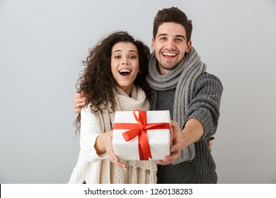 Image of beautiful man and woman rejoicing while standing with present box isolated over gray background