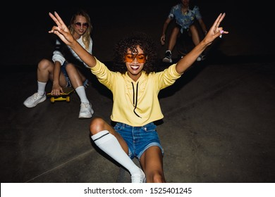 Image of beautiful multinational girls in streetwear smiling and riding on skateboards at night party outdoors