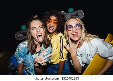Image of beautiful multinational girls in streetwear smiling and holding skateboards at night walk outdoors