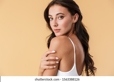 Image of a beautiful pretty young woman in swimwear posing isolated over beige wall background.