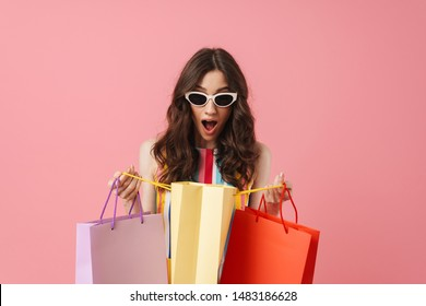 Image of beautiful shocked suprised positive young cute woman posing isolated over pink wall background holding shopping bags.