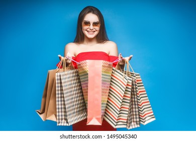Image of a beautiful shocked young woman posing isolated over blue wall background holding shopping bags.