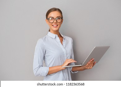 Image of beautiful smiling business woman standing over grey wall background using laptop computer.