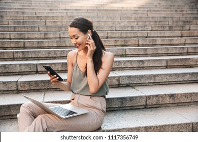 Image of beautiful smiling woman 20s wearing casual summer outfit and bluetooth earphone sitting on street stairs and holding smartphone while using silver laptop