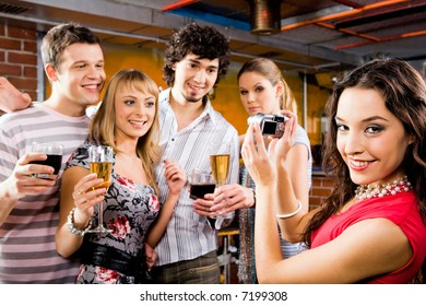 Image of beautiful smiling woman holding the camera at the evening-party
