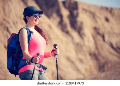 Image of beautiful tourist woman with backpack and walking sticks