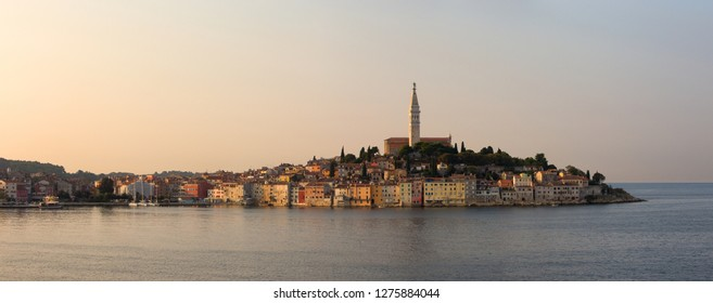 An image of the beautiful waterfront of Rovinj Croatia at dawn in Istria, with the Church of Saint Euphemia atop the hill